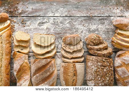 Sliced bread frame on rustic wood background, copy space. Brown and white loaves and flour top view composition with wheat flour sprinkled around.