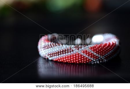 Beaded Bracelet Made Of Red And Brown Beads On A Dark Background