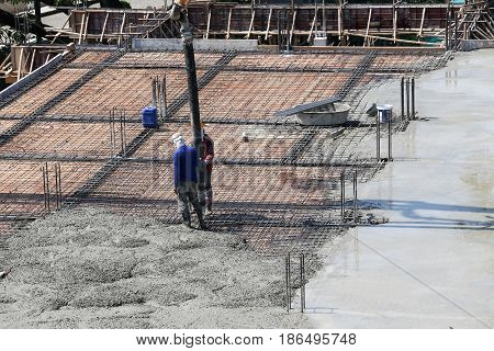 two construction labor work pouring liquid concrete from cement mixer to build floor in construction building