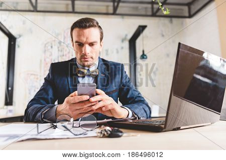 Low angle calm bristled businessman looking at mobile phone while sitting in cozy office