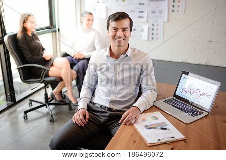 Handsome business man smiling and sit on the chair at the office successful concept
