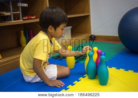 single 8 years old Asian boy playing colorful toy in recreation room