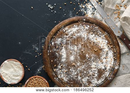 Baking background, flour on board at black. Bakery and home bread making concept. Copy space