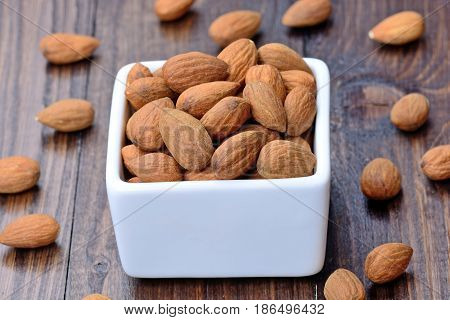 Group of almonds in a ceramic bowl on wooden table