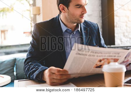 calm bristled male reading article while locating at table in office