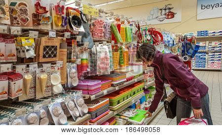 Eskisehir Turkey - April 17 2017: Kitchen utensils for sale on supermarket shelves in Eskisehir Turkey. Young woman shopping in kitchen utensils section in shopping mall.
