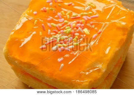 orange butter cake topping colorful candy on wooden chop block