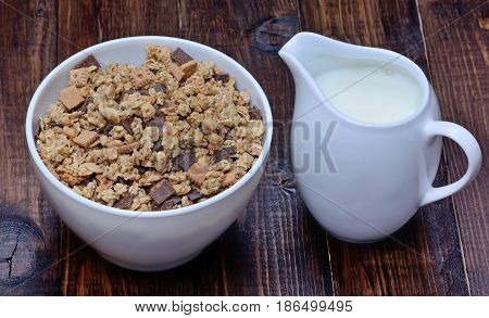 Muesli with chocolate in a bowl with milk on wooden table