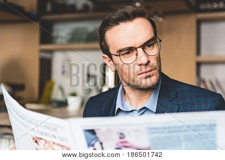 Bristled man expressing composure while looking through article in cozy cafe