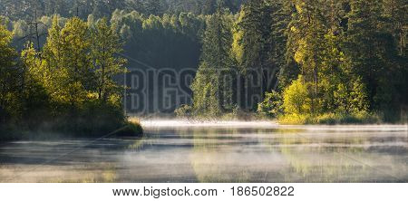 A beautiful Belorussian landscape taken in the region of a thousand lakes, in Belarus. We can see lake and forests with morning's fog. Panorama of  Forest Lake with morning fog and illuminated trees.
