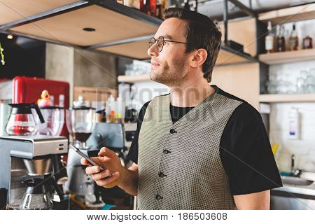 Side view stubbled man expressing thoughtfulness while sending sms by cellphone in comfortable confectionary shop