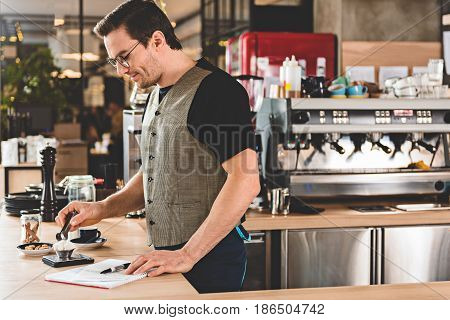 Side view smiling bristled bartender doing mug of delicious hot beverage in confectionary shop. He standing at counter