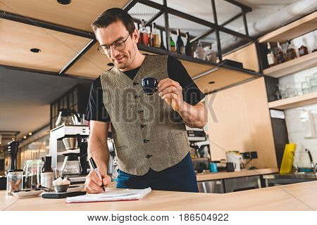 Low angle cheerful stubbled barista writing in copybook while drinking cup of appetizing coffee in cafe