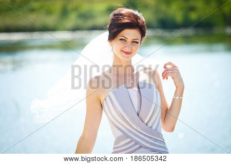 Smiling bride in a violet dress poses in the front of a lake
