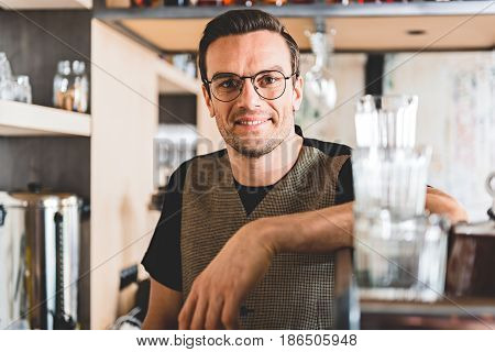 Portrait of happy bristled worker locating in cozy confectionary shop. He looking at camera