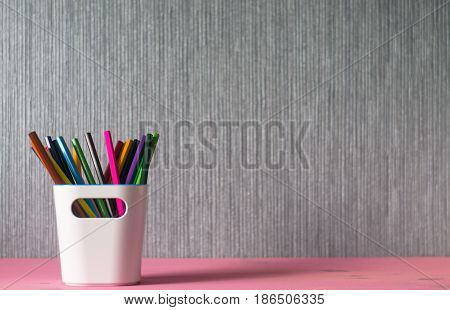 Pencils in white pencil holder on magenta wooden table with silver background.