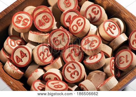 Bowl of lucky round wooden bingo numbers with red numerals for random selection to fill the card in a close up high angle view