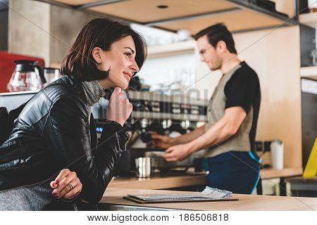Side view smiling client waiting for mug of appetizing beverage in confectionary shop