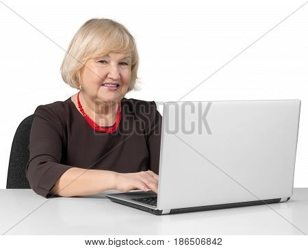 Old Woman Sitting behind Table and Typing on a Laptop - Isolated
