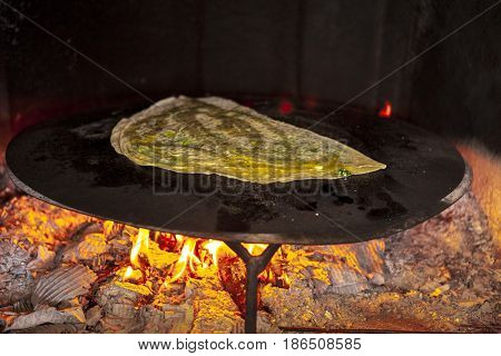Home closed pizza with cheese and parsley fried in a home oven on fire