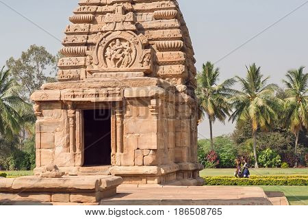 PATTADAKAL, INDIA - FEB 9, 2017: Young women walking past ancient Hindu temple on February 9, 2017. UNESCO World Heritage site with stone carved structures of 7th and 8th-century