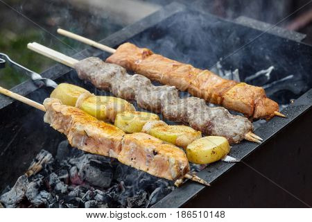 Grilling barbecue of fish potato pork and lula kebabs on skewers