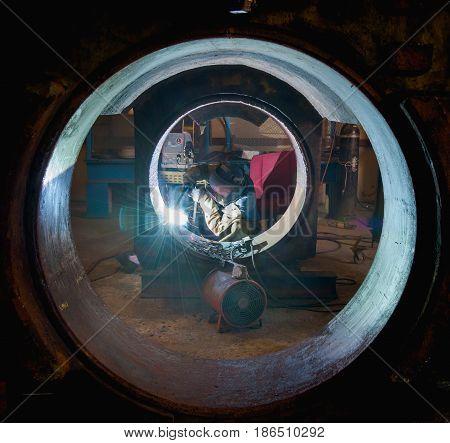 Welder with Flux Core Arc Welding process inside steel structure weld repair in fabrication factory.