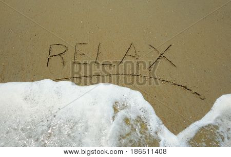 Relax written in the sand with ocean wave