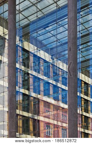 Disappearing glass lines of an office building. Vertical glass facade with blue tinted large windows