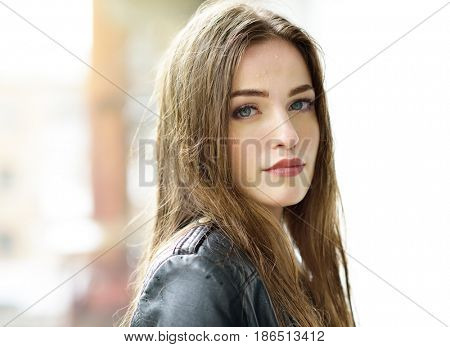 Young attractive woman standing in the rain directing her face to the drops. Girl in rainy day gets wet, image toned, soft focus. Beautiful female face.