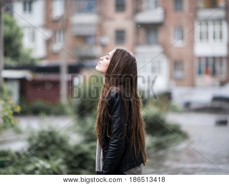 Young attractive woman standing in the rain directing her face to the drops. Girl in rainy day gets wet, image toned, soft focus