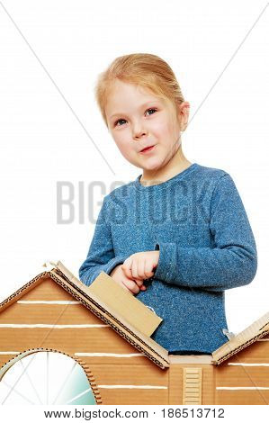 Pretty little blonde girl in a blue shirt peeks out from behind the cardboard house.Isolated on white background.