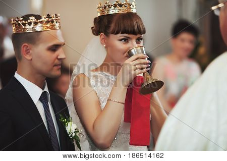 Bride Looks At A Pries Drinking Holy Wine