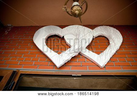 Huge cloth hearts hang under the ceiling outside