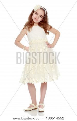 A nice little school-age girl in a smart white dress.Photo in full growth.Isolated on white background.
