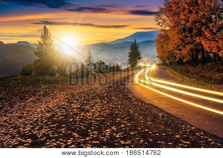 countryside road with car lights. beautiful autumn mountain landscape at sunset