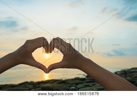 Female hands in the form of heart against sunlight in sunrise sky on beach morning time. Hands in shape of love heart Love concept.