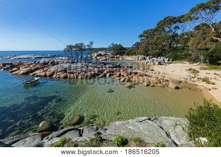 Pretty Coastal scene with turquoise waters rippled sparkled, orange lichen growing on granite rocks formations, rocky coastline at Skeleton Bay, part of Binalong Bay, Bay of Fires, Tasmania, Australia
