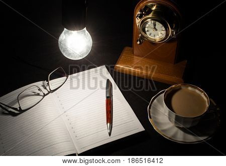 Open diary book with empty pages white cofee cap pencilglasses and wooden clock on black background under lights of switched on bulb. Business or education concept.