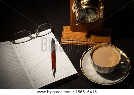 Open diary book with empty pages white cofee cap pencilglasses and wooden clock on black background. Business or education flat layout.