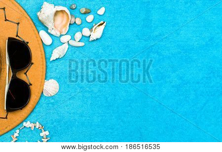 Orange hat pebbles seashells and glasses on blue towel (washcloth) background. Sea vacation flat layout background concept. Top view.