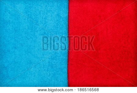 Two towels (washcloths) close up texture. Red towel and blue towel makes vertical line. Abstract background. Top view.