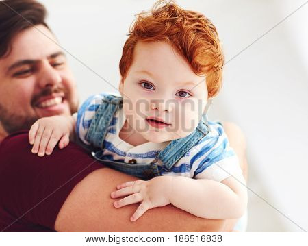 Portrait Of Adorable Red Head Infant Baby Boy On Father's Hand