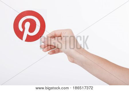 KIEV, UKRAINE - AUGUST 22, 2016: Woman hands holding Pinterest icon printed paper close up. Is photo sharing website.