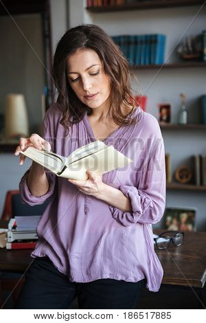 Portrait of a thoughtful mature woman reading book while leaning on a table indoors