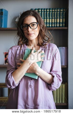 Portrait of a smiling mature woman in glasses holding book while standing near bookshelf and looking at camera