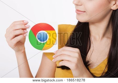 Kiev, Ukraine - August 22, 2016: Woman hands holding colorful Google Chrome icon printed on paper on grey background.Google is USA multinational corporation.