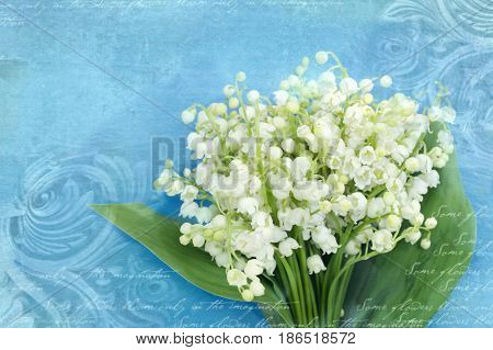 Bouquet of lilies of the valley on a grunge blue background with architectural details meander capitals friezes. Art deco figures carved on stone. Fragment of ornate relief with flowers.