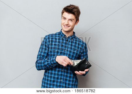 Image of young happy man standing over grey wall and looking at camera while holding purse with money.