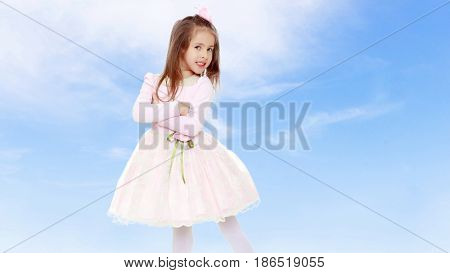 Dressy little girl long blonde hair, beautiful pink dress and a rose in her hair.One folded his arms.